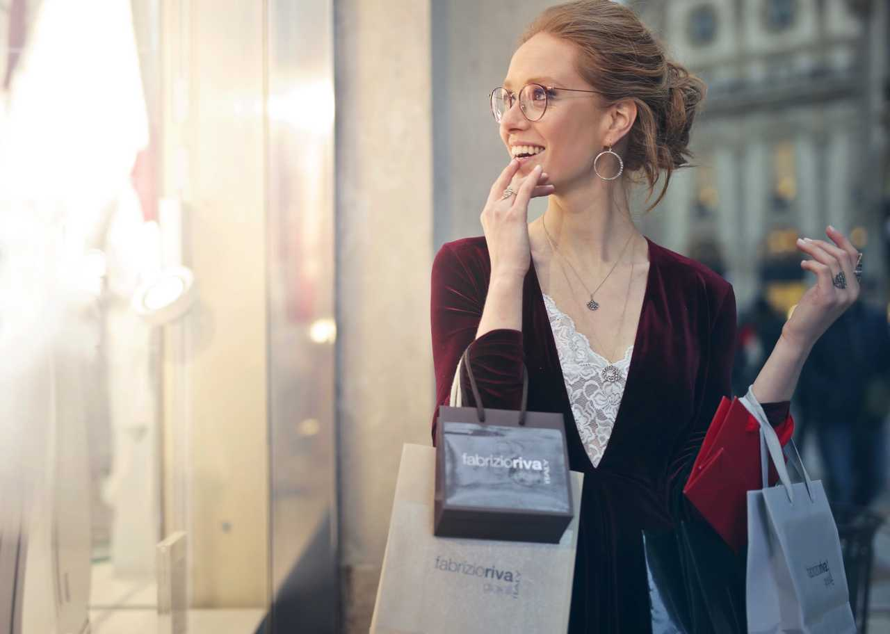 woman with shopping bags attracted by shiny shop window